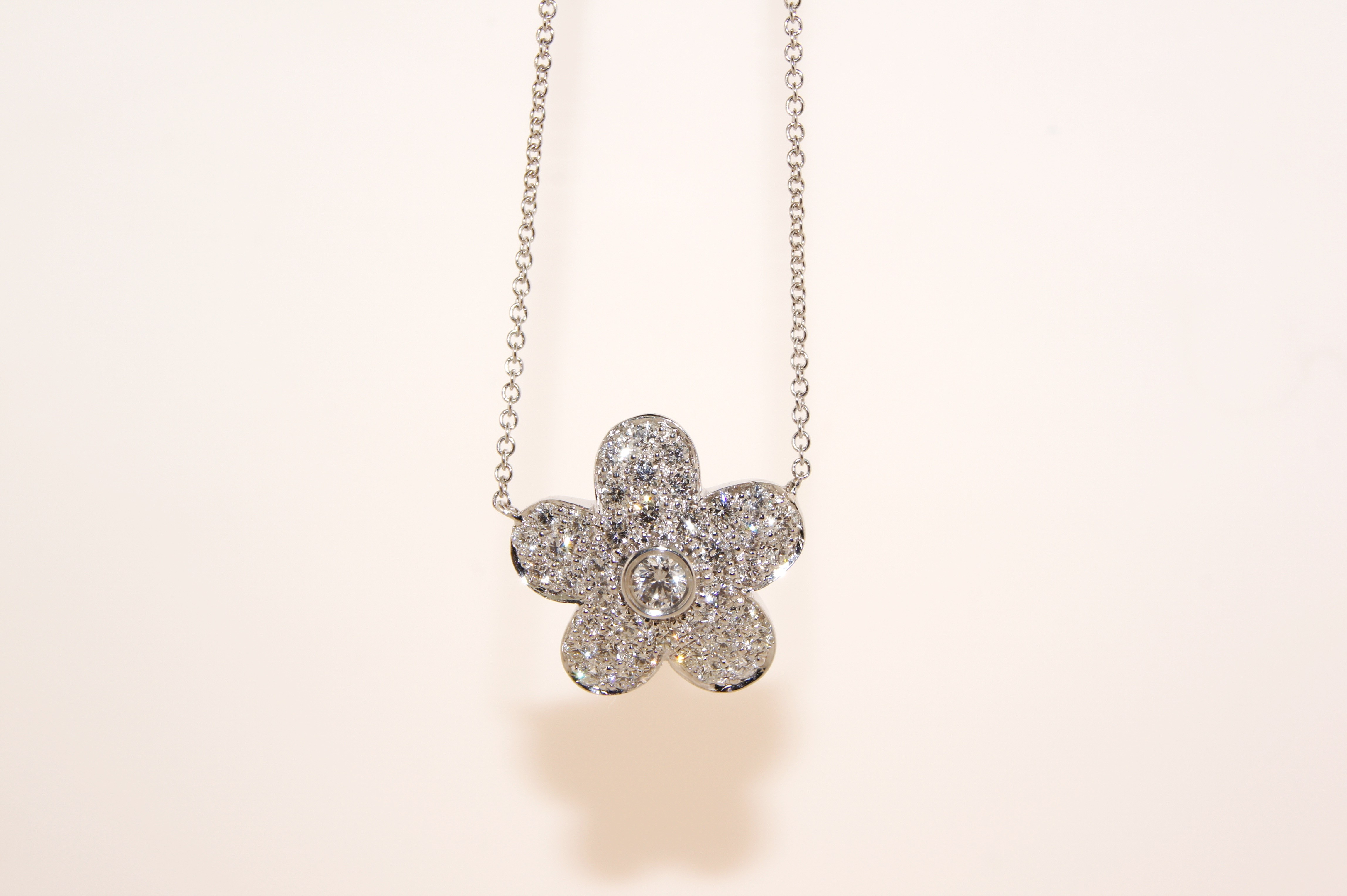 18 karat white gold diamond flower necklace.