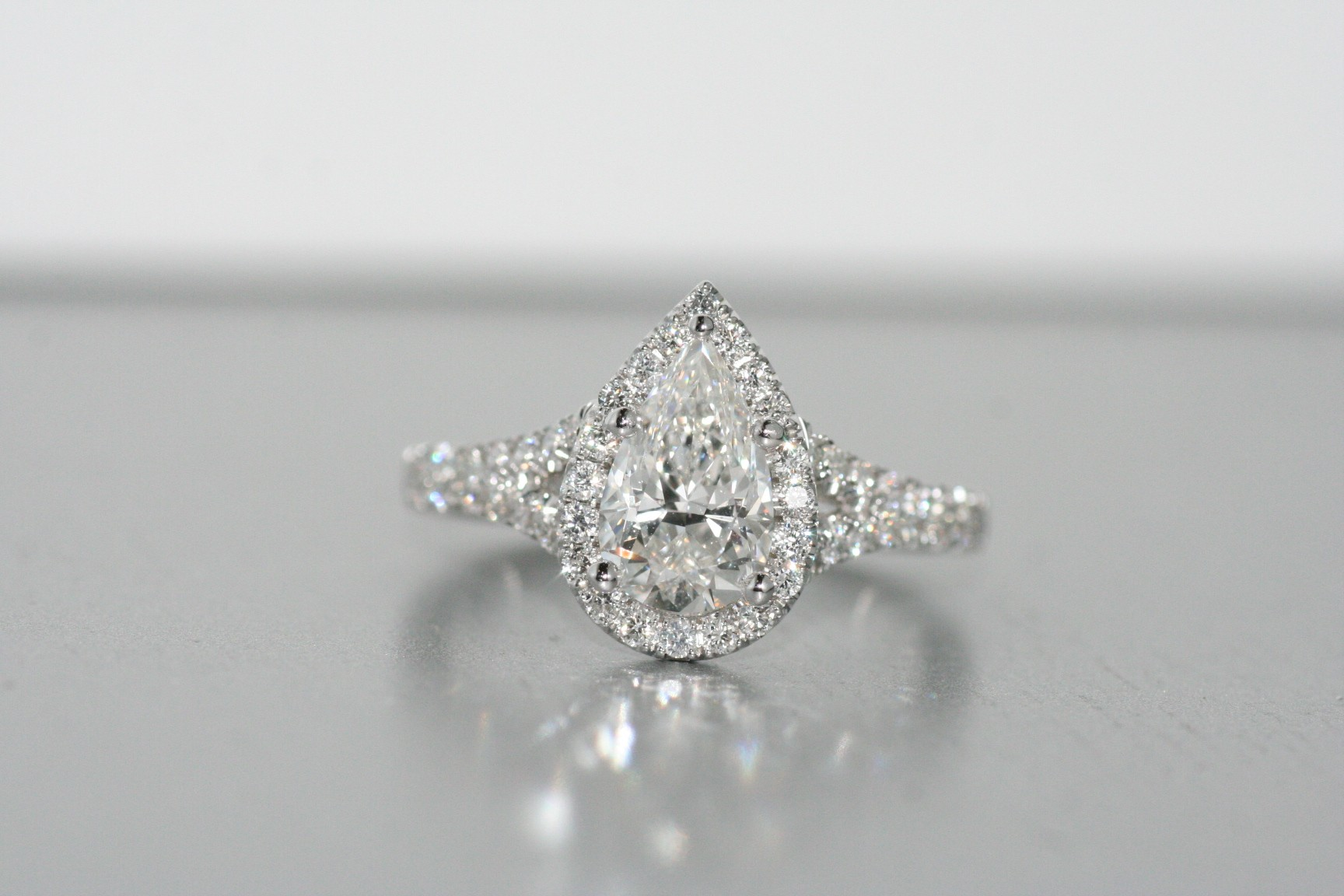 Platinum halo diamond ring with pear shape.