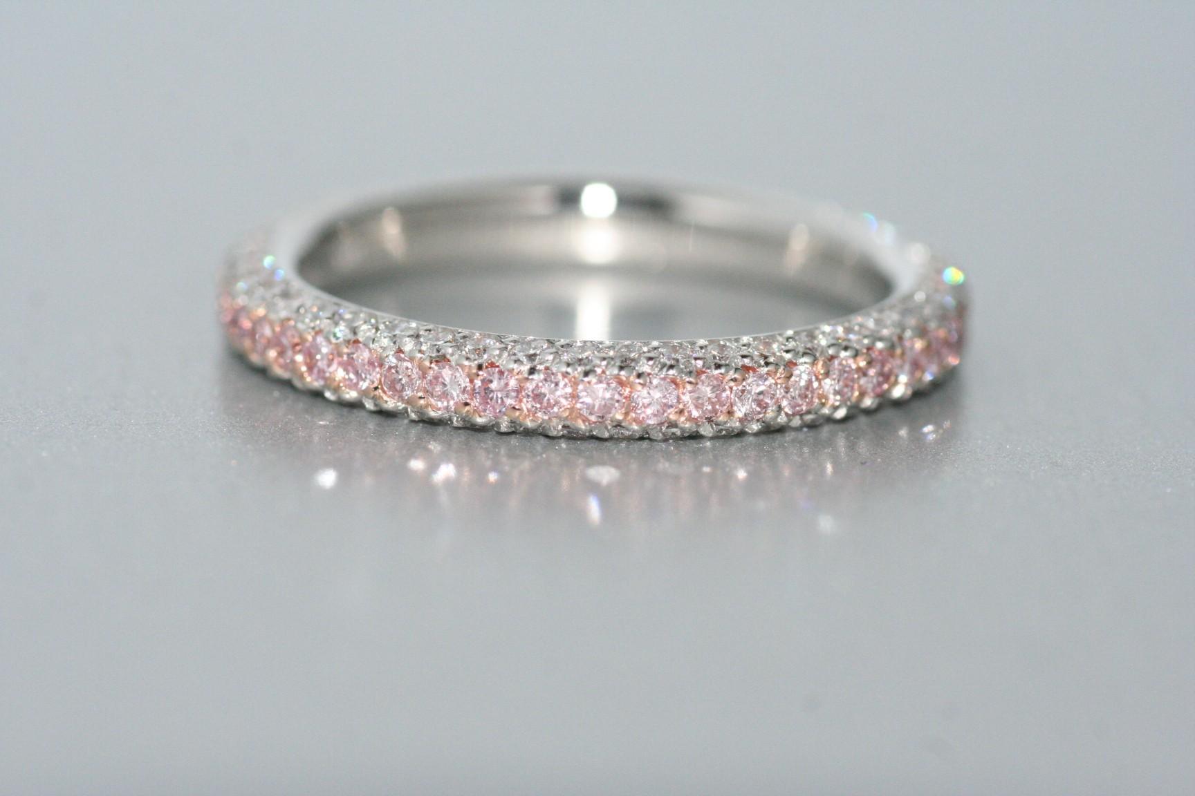 Platinum diamond eternity band with pink and white diamonds.